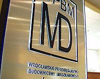 Srebrny metalowy kaseton z wypukłymi granatowymi podświetlanymi literami