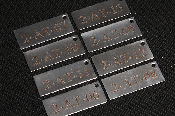 Grawerowanie numerów na metalowych zawieszkach do kabli
