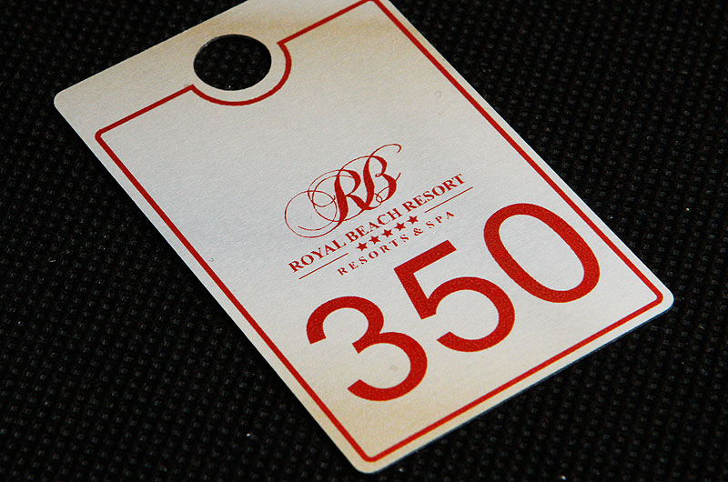 Metalowy numerek do szatni w hotelu spa, w kolorze srebrno bordowym, drukowany, nieścieralny
