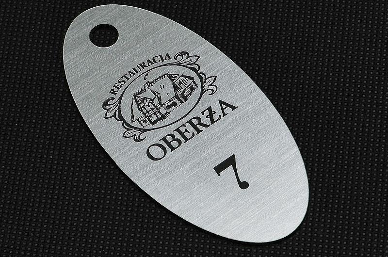 Owalny numerek do szatni w restauracji, srebrno czarny laminat grawerowany