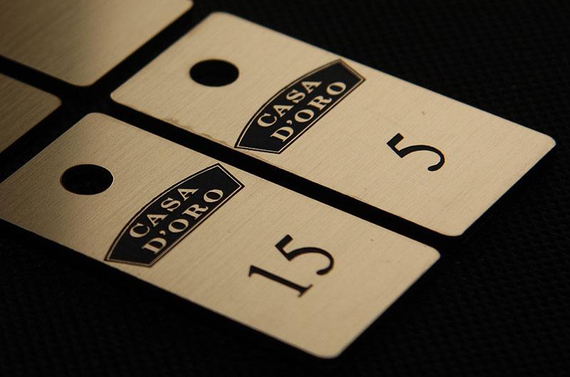 Złoto czarne numerki do szatni w restauracji, grawerowane na laminacie