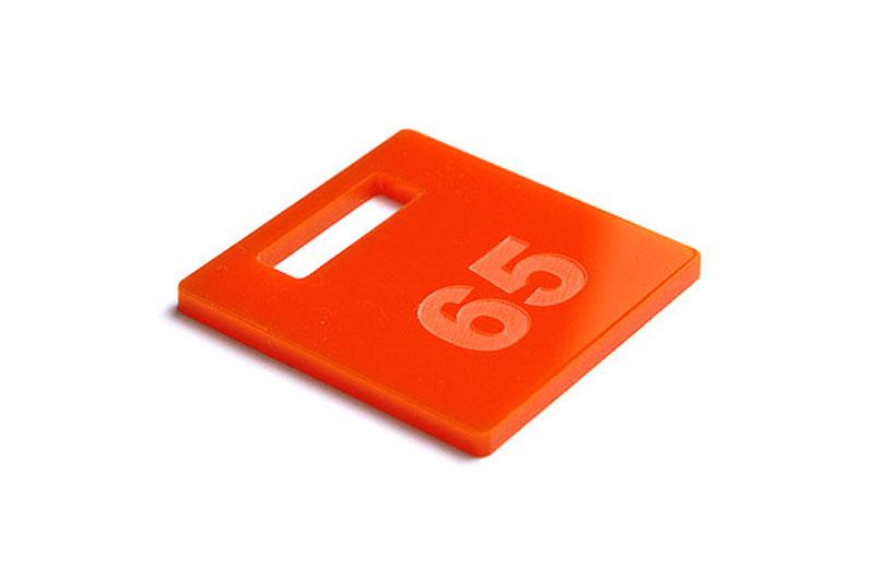 Pomarańczowy numerek do szatni z pleksi grawerowany laserem