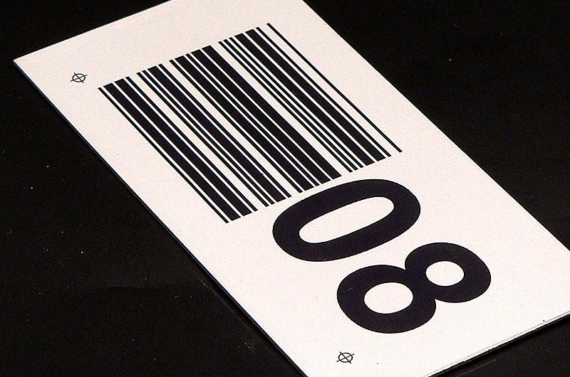 Metalowy numerek z kodem kreskowym na regał magazynowy