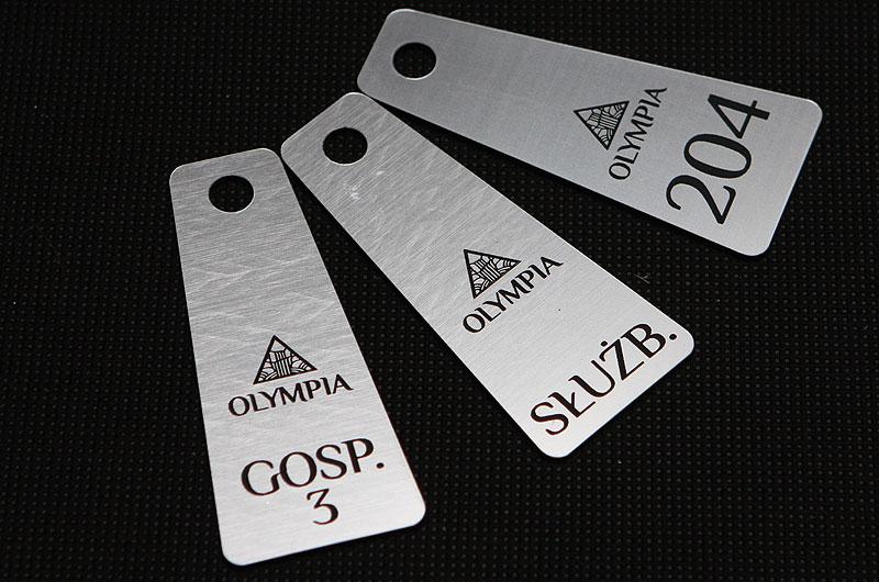 Plastikowe numerki do kluczy ze znakiem firmowym i opisem pomieszczeń w kolorze srebrno czarnym