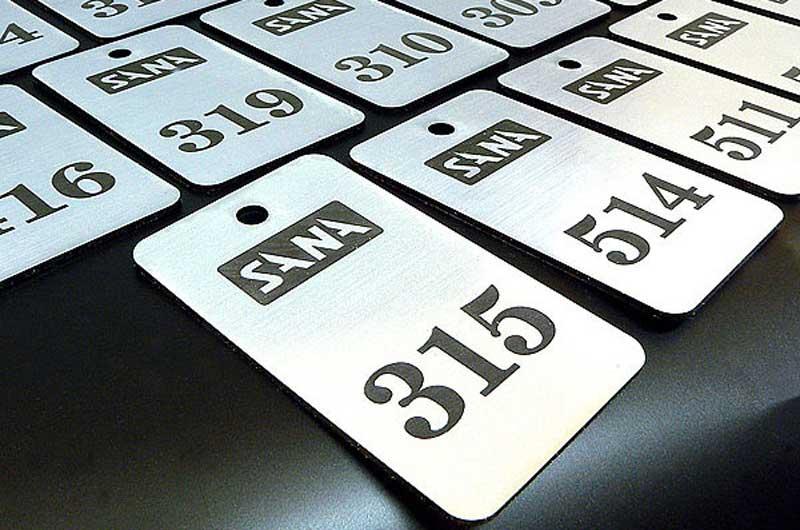 Grawerowane srebrno-czarne numerki do kluczy dla hotelu