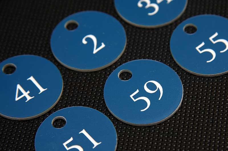 Grawerowane niebiesko-białe zawieszki z numerami do kluczy do szafek w szkole