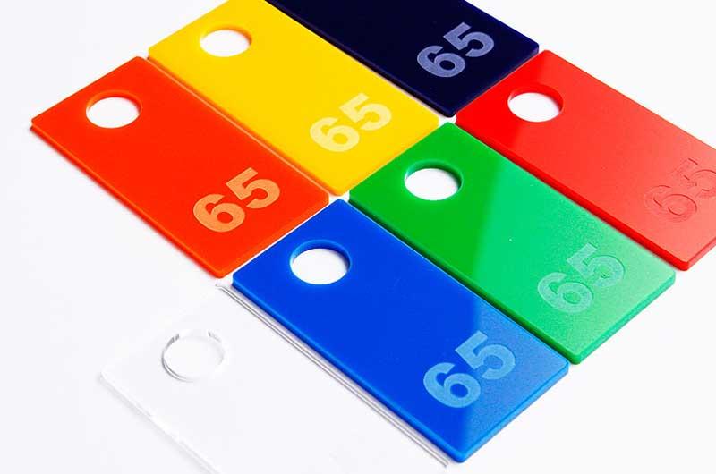 Prostokątne numerki do kluczy grawerowane na pleksi z dużym otworem