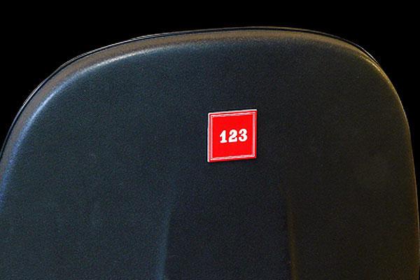 Numerek zamontowany na oparciu krzesła