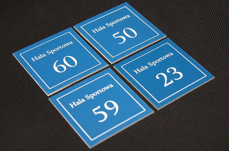 Kwadratowe grawerowane numerki na drzwi hali sportowej