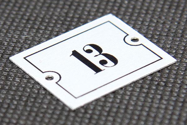Metalowy numerek na szafkę stadionową, mocowany na śruby, srebrno-czarny, prostokątny