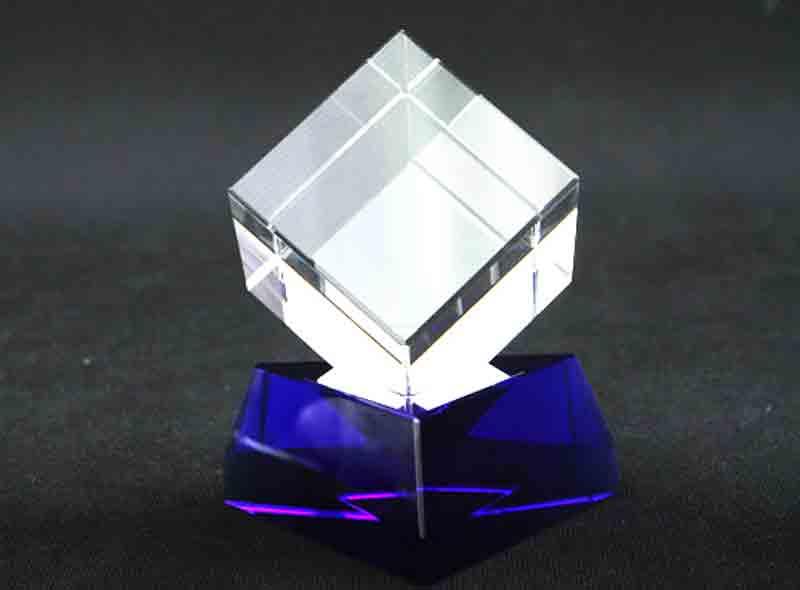 Szklana statuetka sześcian na trójkątnej granatowej podstawce widok z przodu