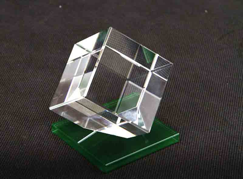 Statuetka szklana sześcian na zielonej podstawce widok z boku
