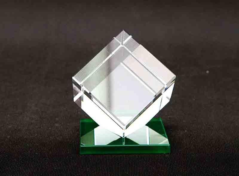 Statuetka szklana sześcian na zielonej podstawce widok z przodu